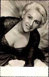 Ansichtskarte / Postkarte Schauspielerin Martine Carol, Frau im Kleid sitzt auf einem Bett, Dekolleté