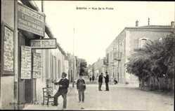 Postcard Biskra Algerien, Rue de la Poste, Poststraße, Ansichtskartenverkauf