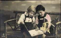 Ak Zwei Mädchen auf einer Bank ein Buch lesend, Puppe