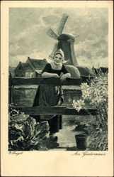 Künstler Ak Louyot, E., Am Gartenzaun, Niederländ. Tracht, Windmühle